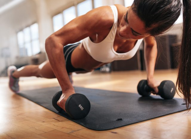 Woman with strong muscle arms doing push ups for exercise
