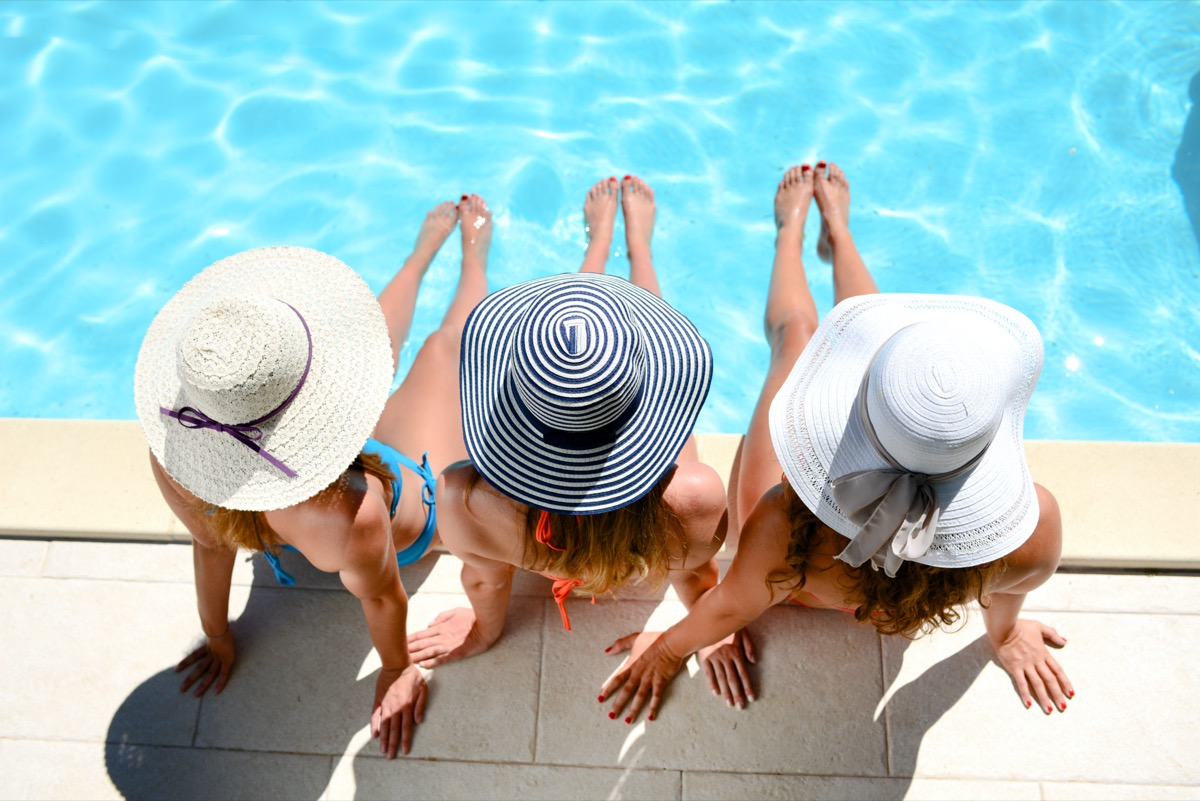 Three women wearing sun hat sitting by the poolside of a resort swimming pool during summer holiday.