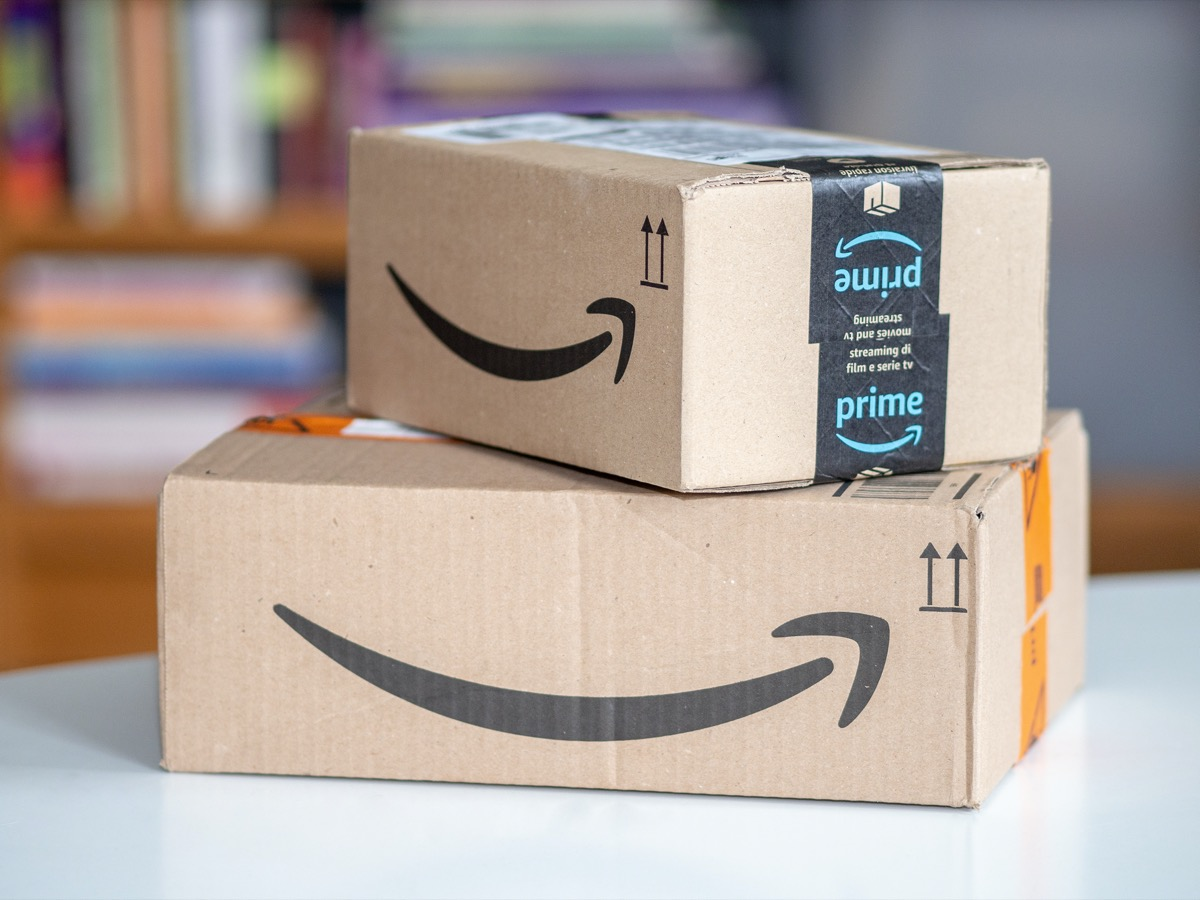 Amazon shipping box on a wooden floor in front of a door inside a house.