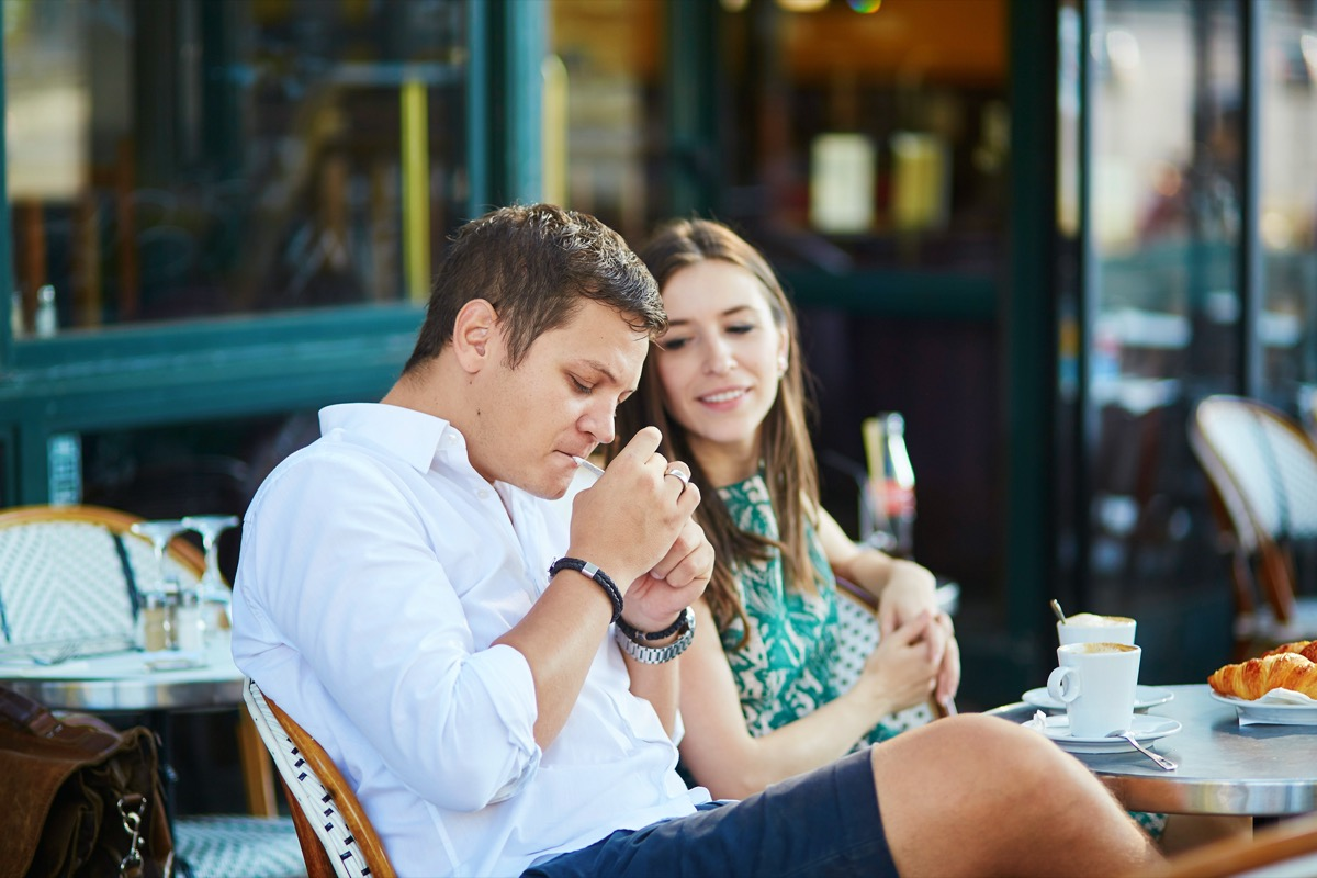 Young romantic couple drinking coffee, eating traditional French croissants and smoking in a cozy outdoor cafe in Paris, France