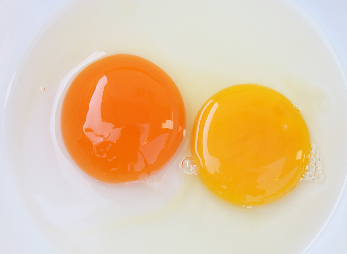 two different egg yolk colors in a bowl
