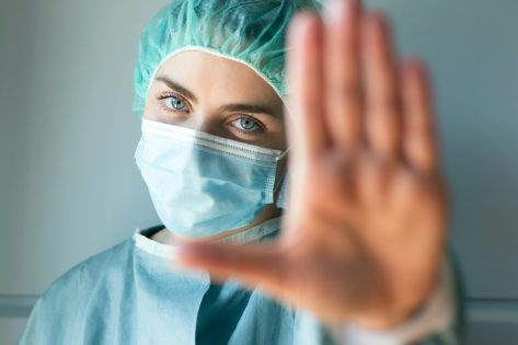 Caucasian young female doctor looking in camera while making stop sign with hand.