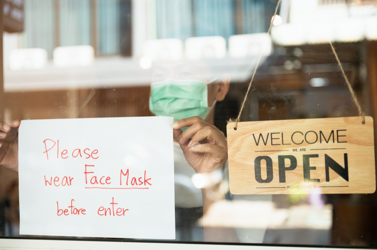 restaurant shop owner woman attaching request customer to wear face mask before enter