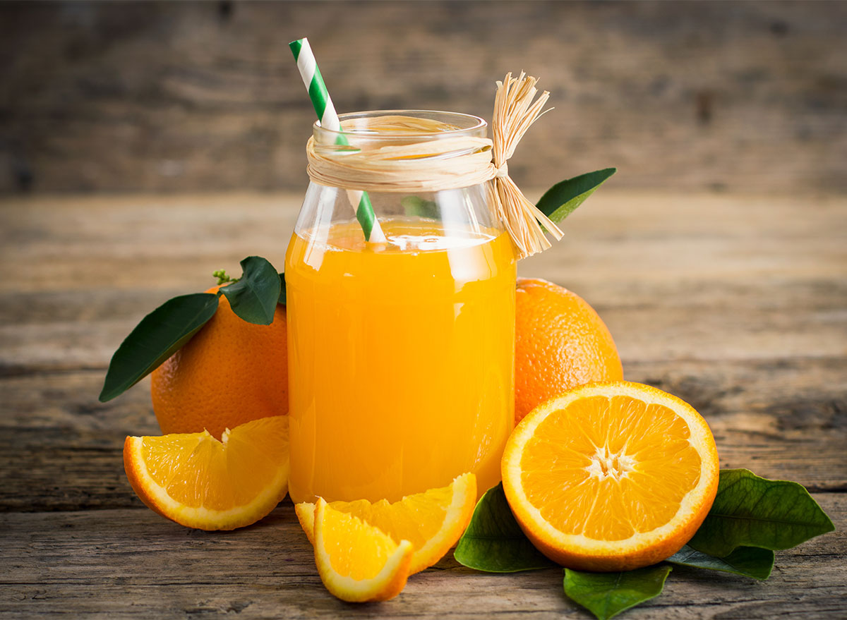 jar of fresh squeezed orange juice with cut orange halves