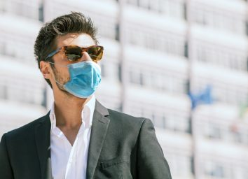 man with surgical face mask and sunglasses outdoors