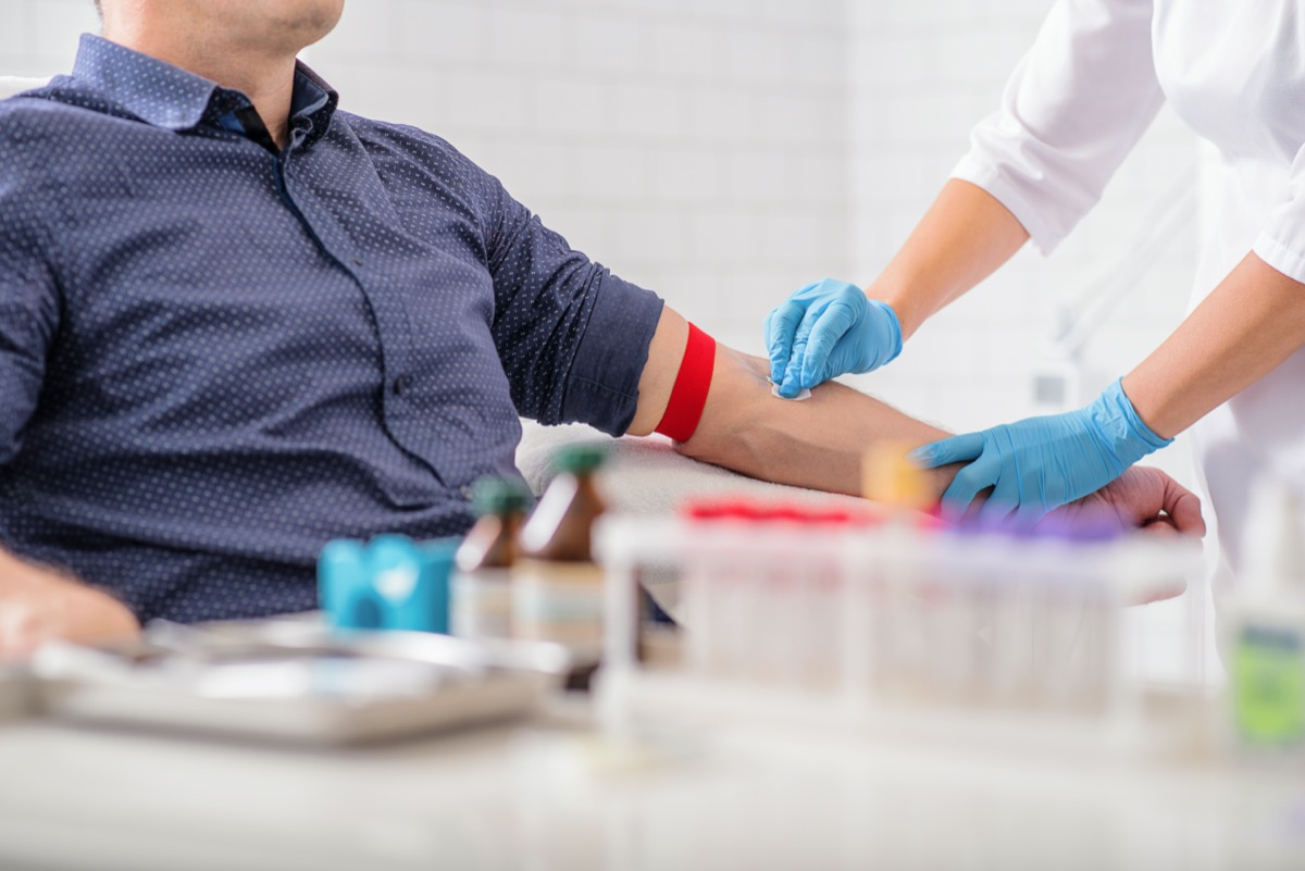 nurse disinfecting male arm before blood