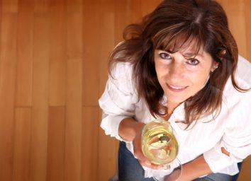 Mature woman with a glass of white wine.