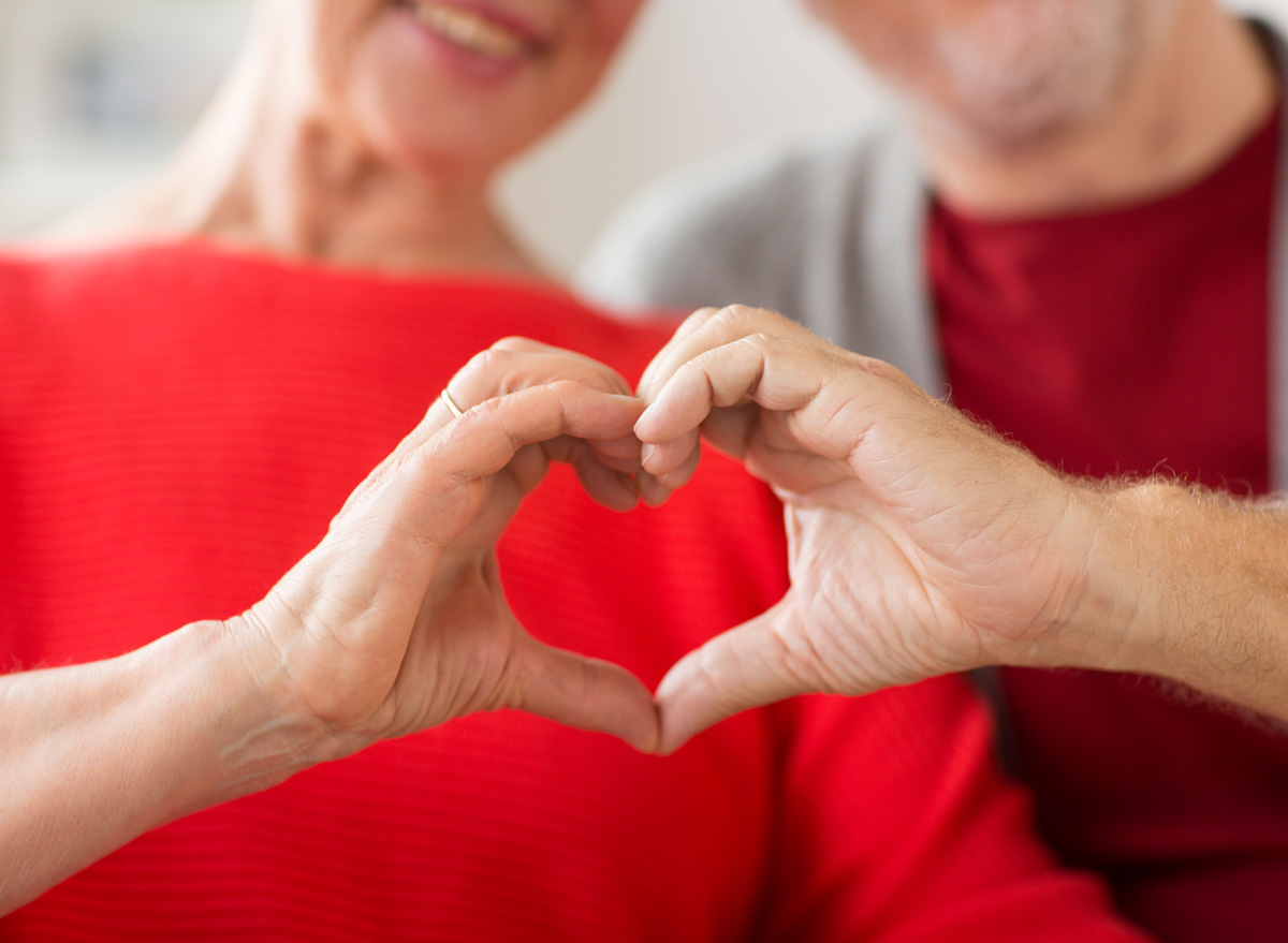 Older man and woman holding hands in shape of heart for good heart health
