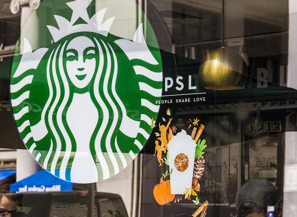outside starbucks with a pumpkin spice latte sign