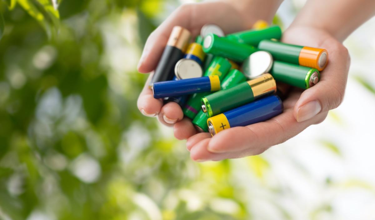 hands holding alkaline batteries