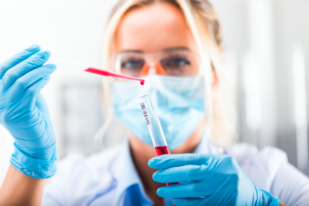 Young attractive concentrated female scientist in protective eyeglasses, mask and gloves dropping a red liquid substance into the test tube with a pipette in the scientific chemical laboratory