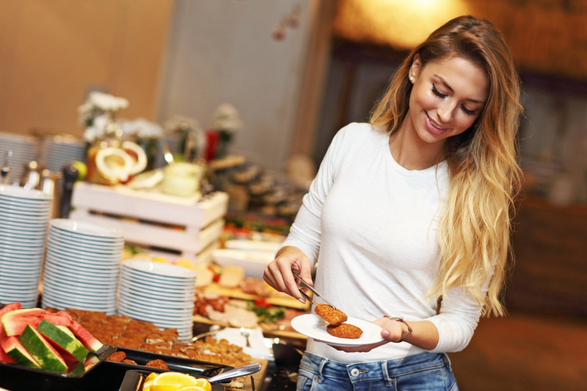Picture of attractive woman at breakfast buffet in hotel