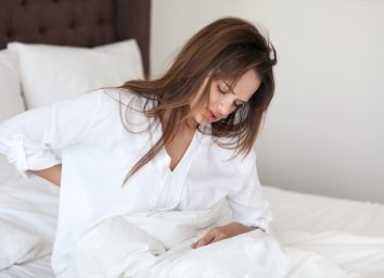 woman stretching in bed feeling morning discomfort