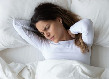 Woman feeling neck ache, suffering from painful feeling in neck