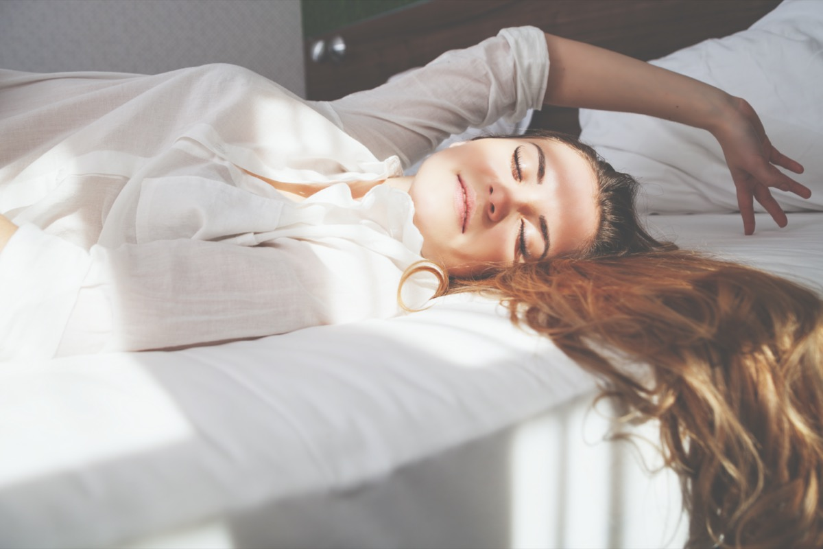 Pretty young woman on bed in modern apartment smiling after wake up