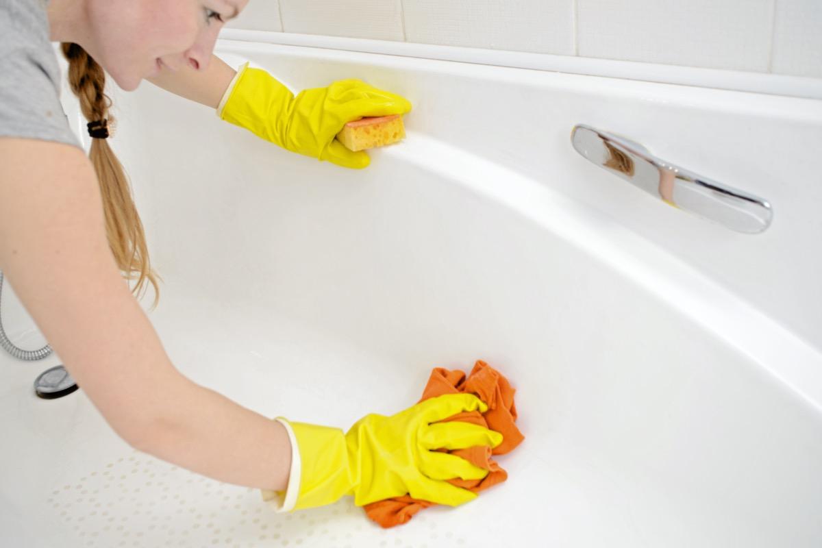 Female washing bathtub in yellow rubber gloves with orange sponge.
