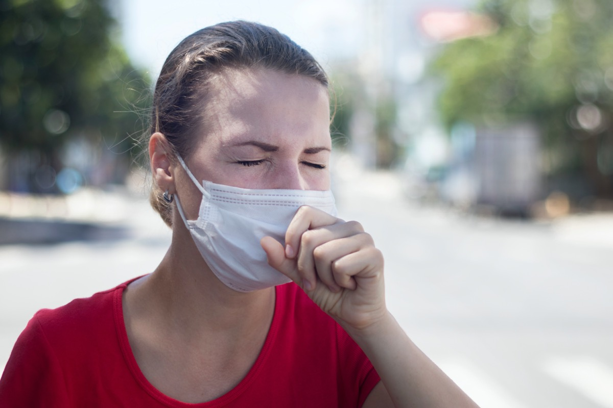 woman coughing in medical mask on her face