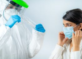 Medical worker in protective suite taking a swab for corona virus test, potentially infected young woman