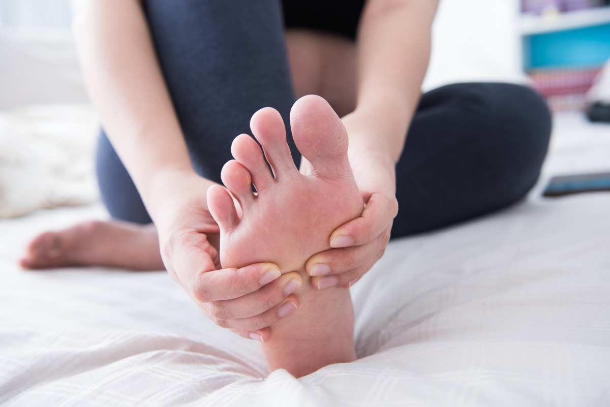 Woman holding feet toes