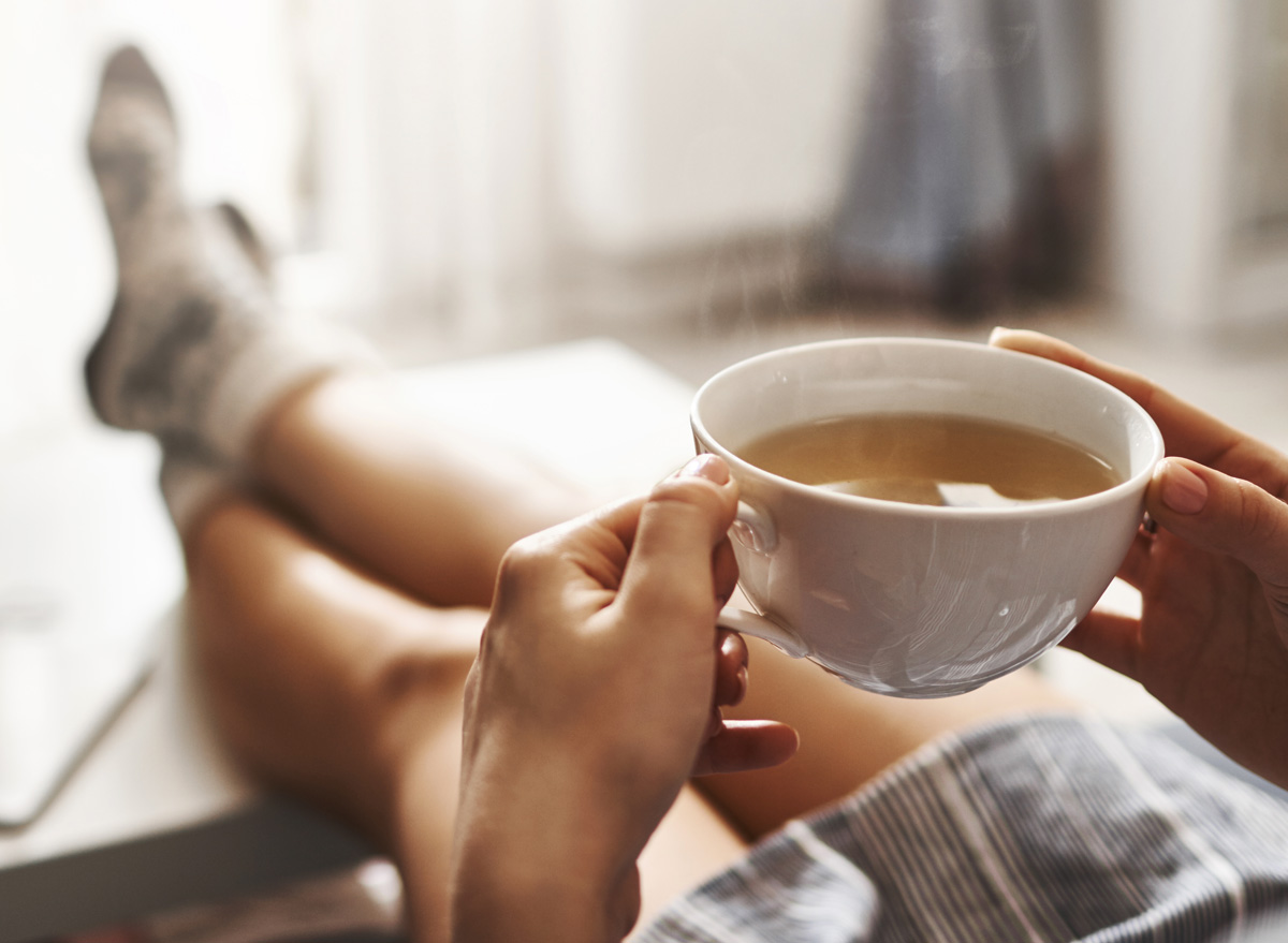 Woman drinking tea relaxing on couch