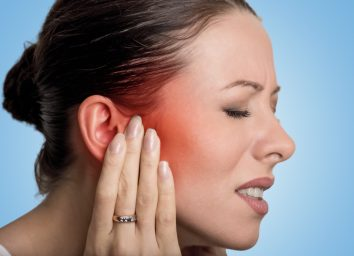 female having ear pain touching her painful head