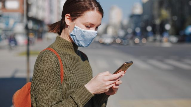 Woman face mask phone checking