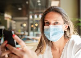 Woman in a face mask sitting at a bar, looking at the camera while holding her smart phone in her hands