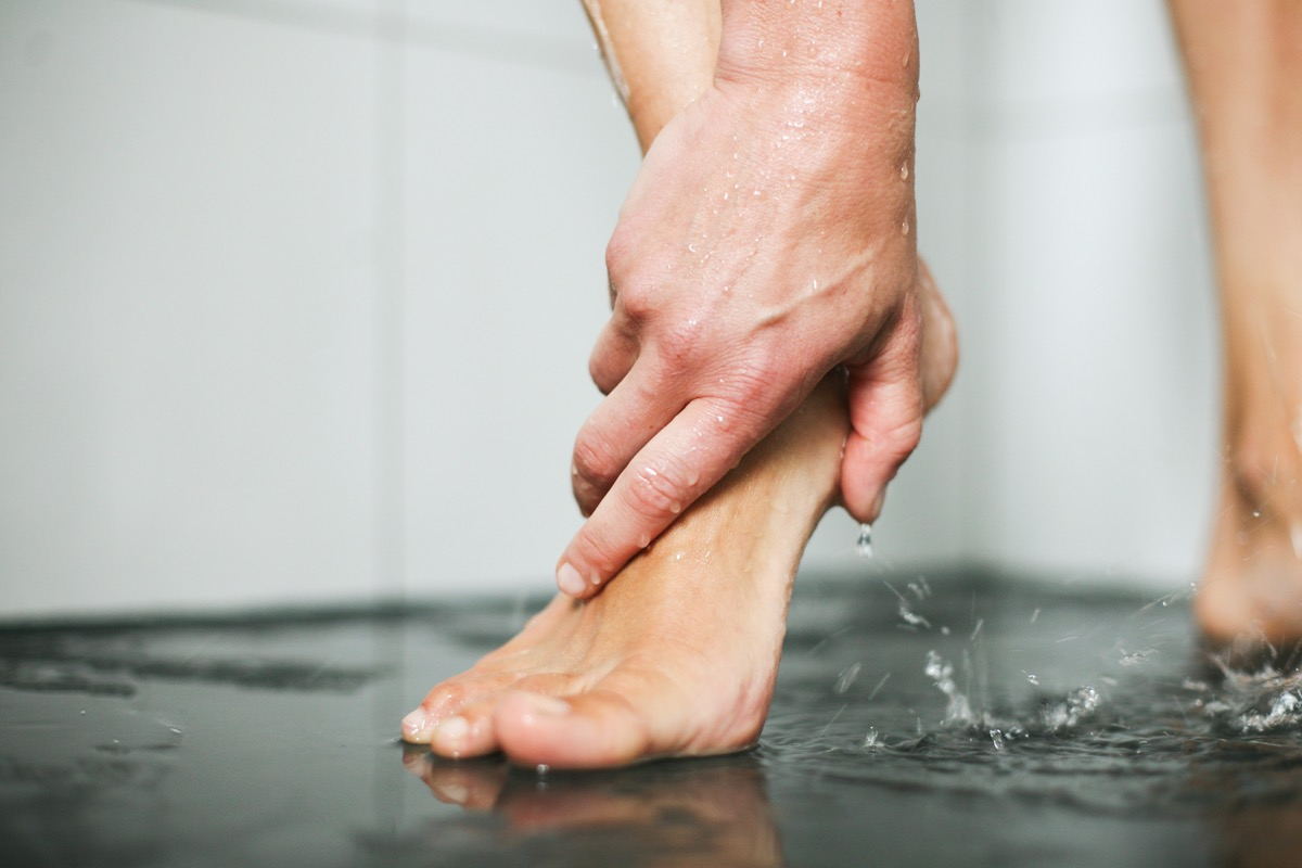 Woman washes her feet in shower