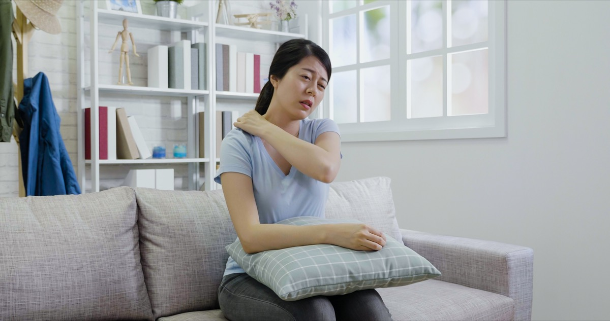 female touching neck and shoulder in pain.