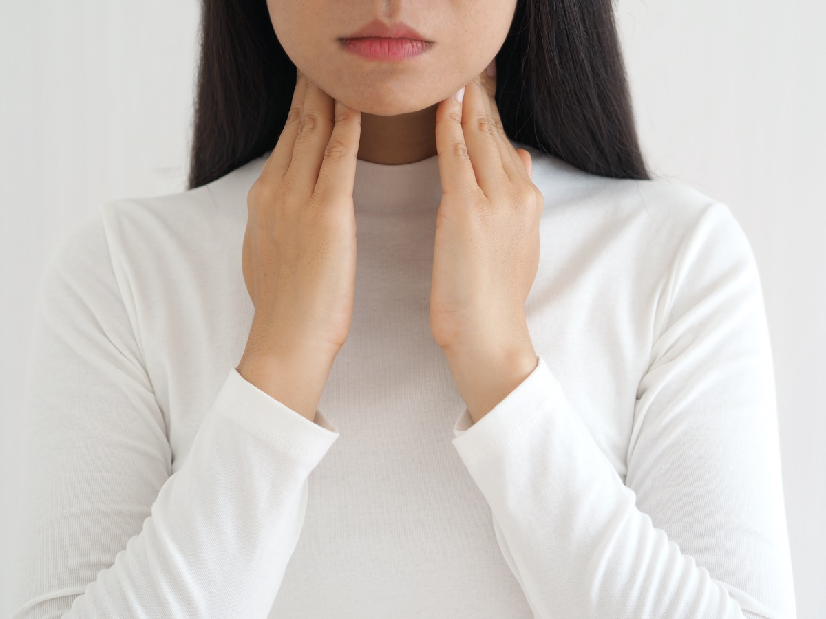 woman touching neck with her hands.