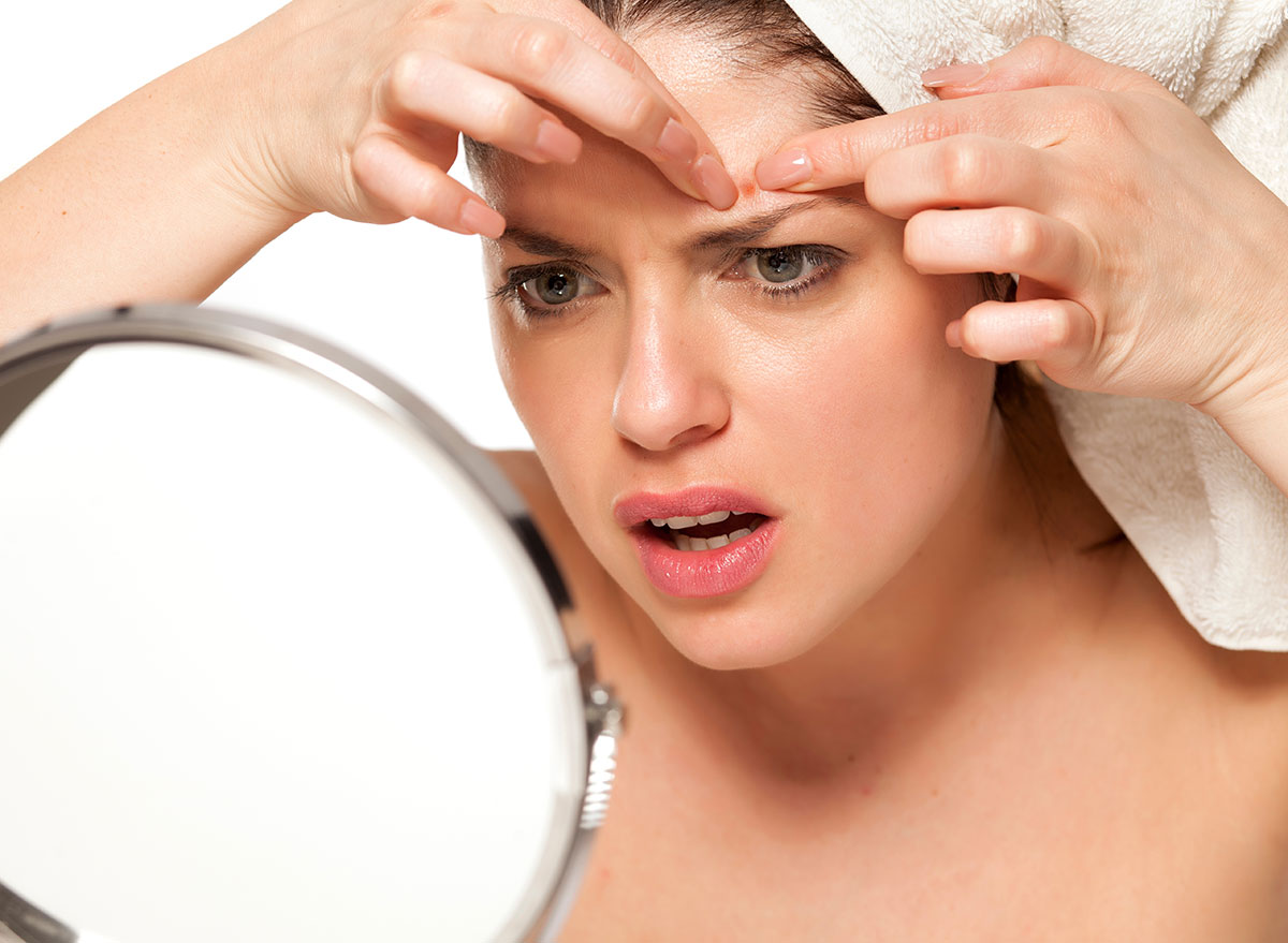 woman popping pimple