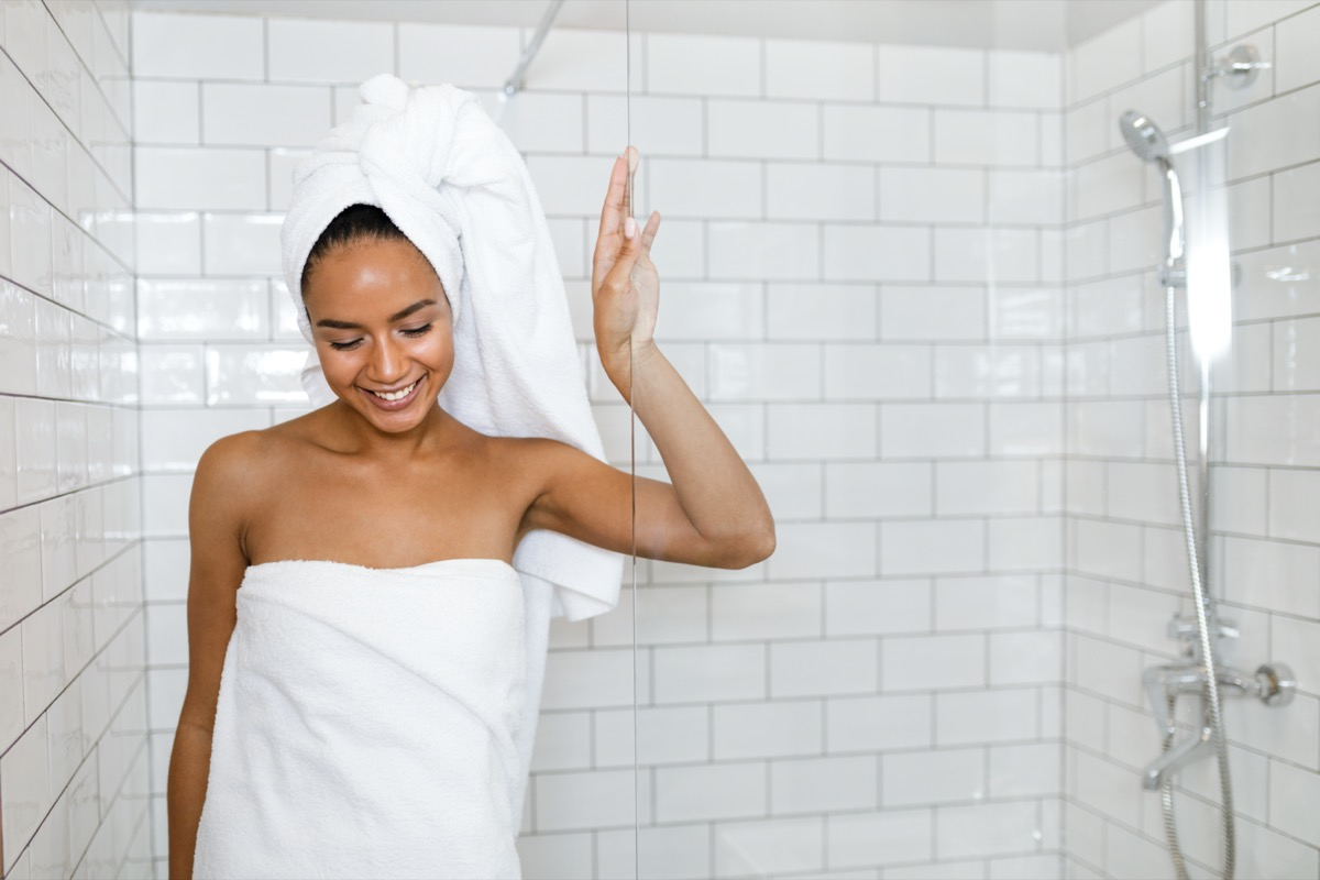 woman in white towels wrapped around head and body after shower.