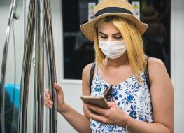 woman wears face mask and keeps social distance by standing and using smart phone while transporting at train