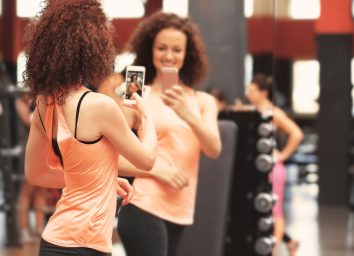 Woman taking mirror selfie at a gym showing off her weight loss