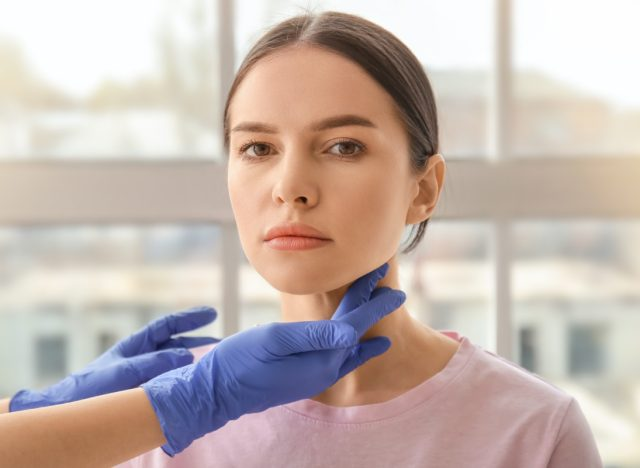 Endocrinologist examining thyroid gland of young woman in clinic