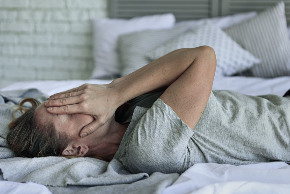 Fatigued woman lying at bedstead