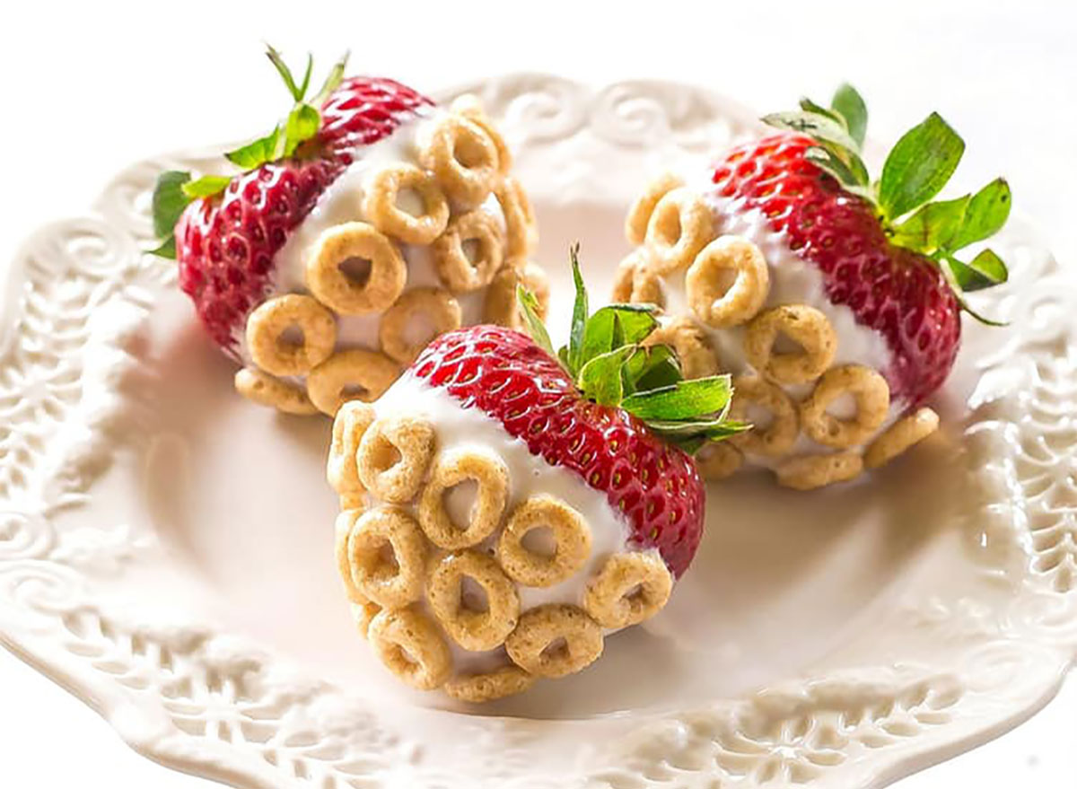whole strawberries dipped in yogurt and covered with cheerios on white serving plate