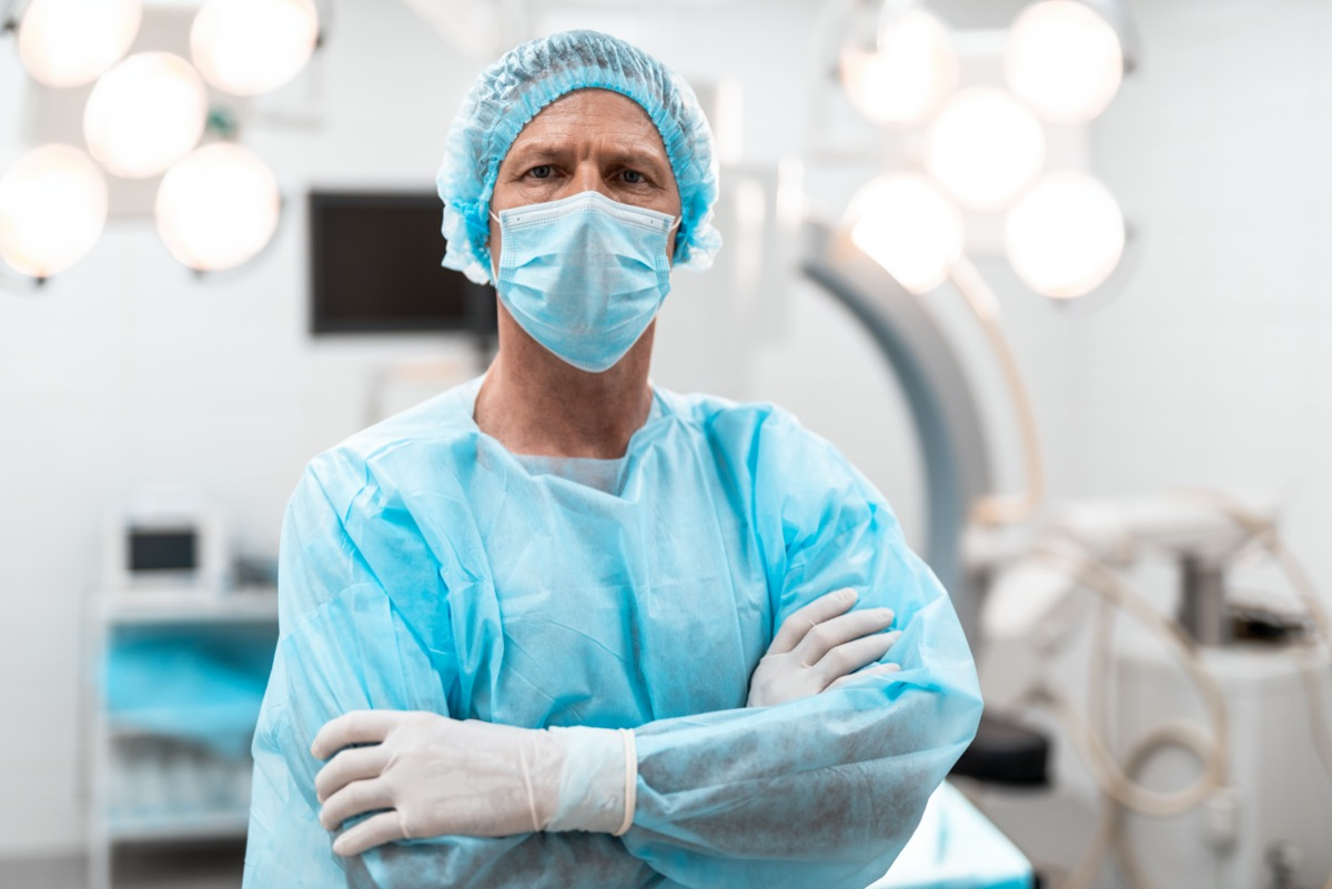Confident experienced doctor in blue medical uniform frowning while standing with his arms crossed