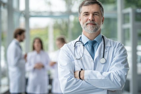 Confident smiling doctor posing in the hospital with medical team working on the background