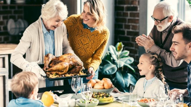 grandmother carrying turkey for family on thanksgiving dinner