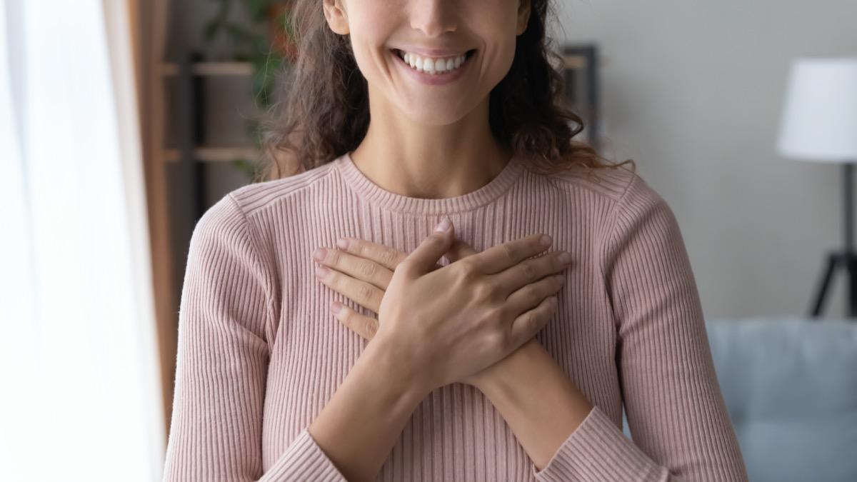 female holding folded hands on chest