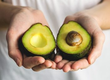 Hold avocado cut open in hand