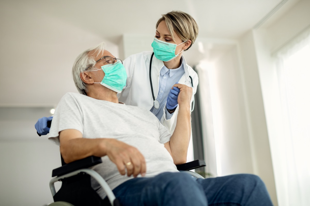 female doctor holding hands with senior man in wheelchair