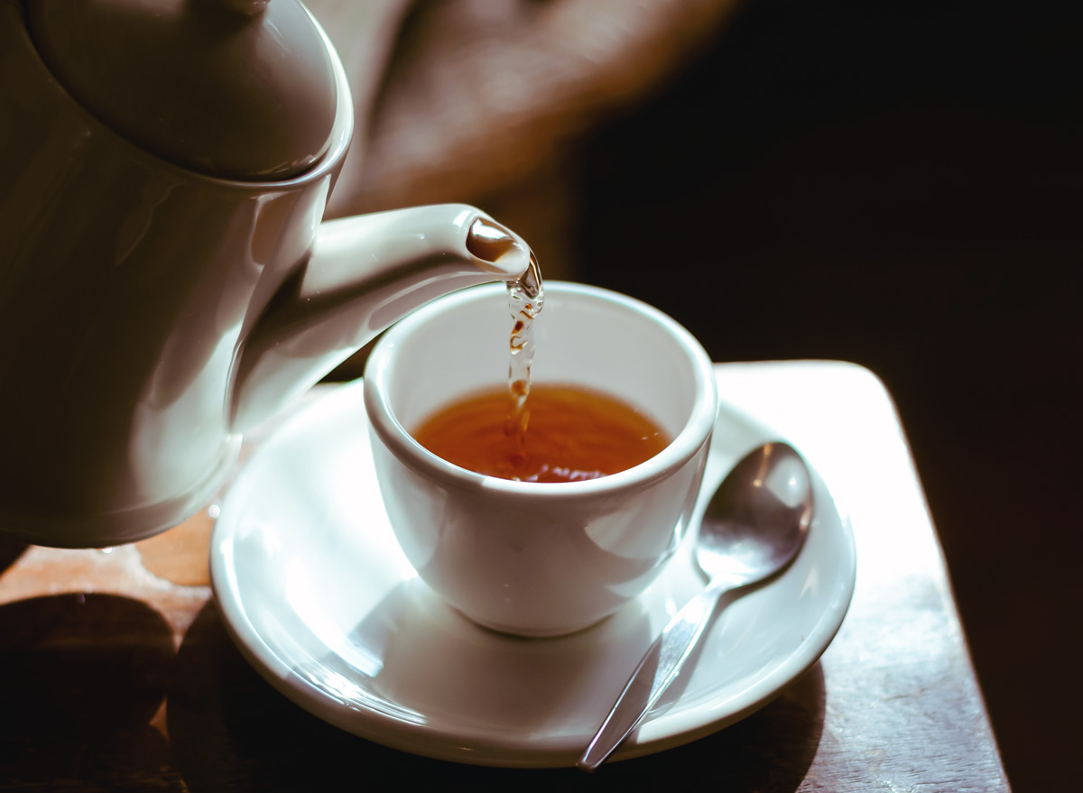 pour cup tea from tea pot