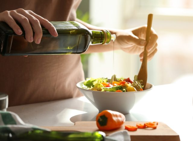 pouring extra virgin olive oil on a veggie salad