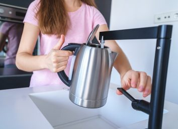 Pouring tap water into a tea kettle to boil