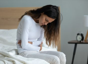 Unhealthy woman sit on bed touch stomach