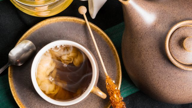 Milk and honey and crystalized sugar stick to flavor a cup of tea