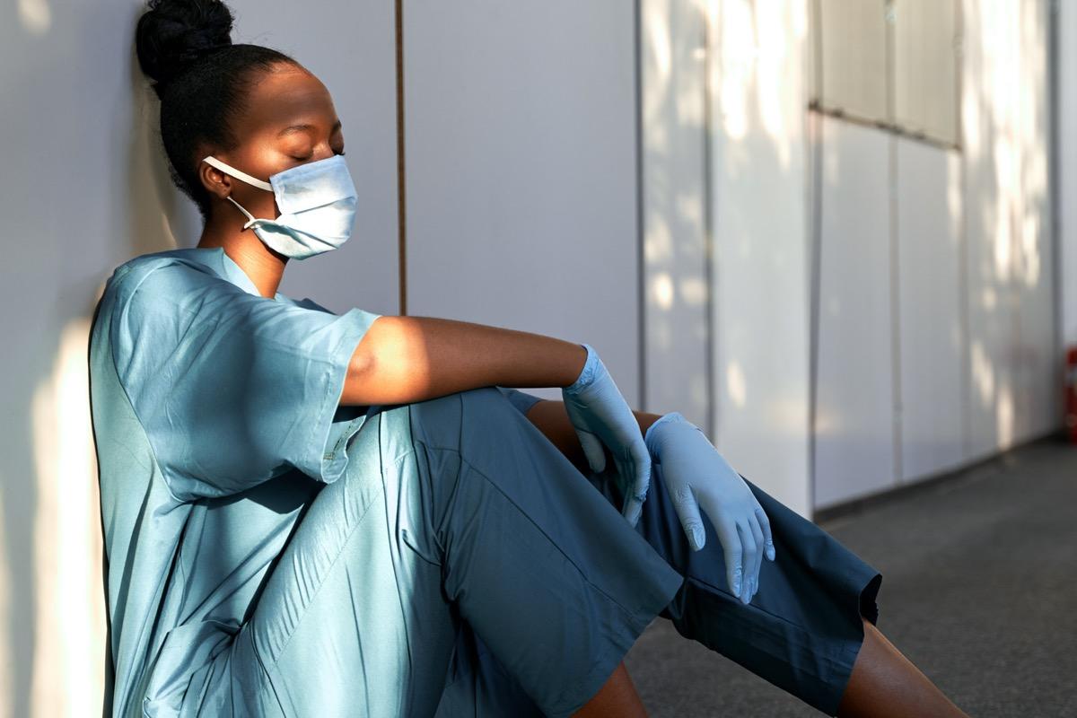 Tired exhausted female scrub nurse