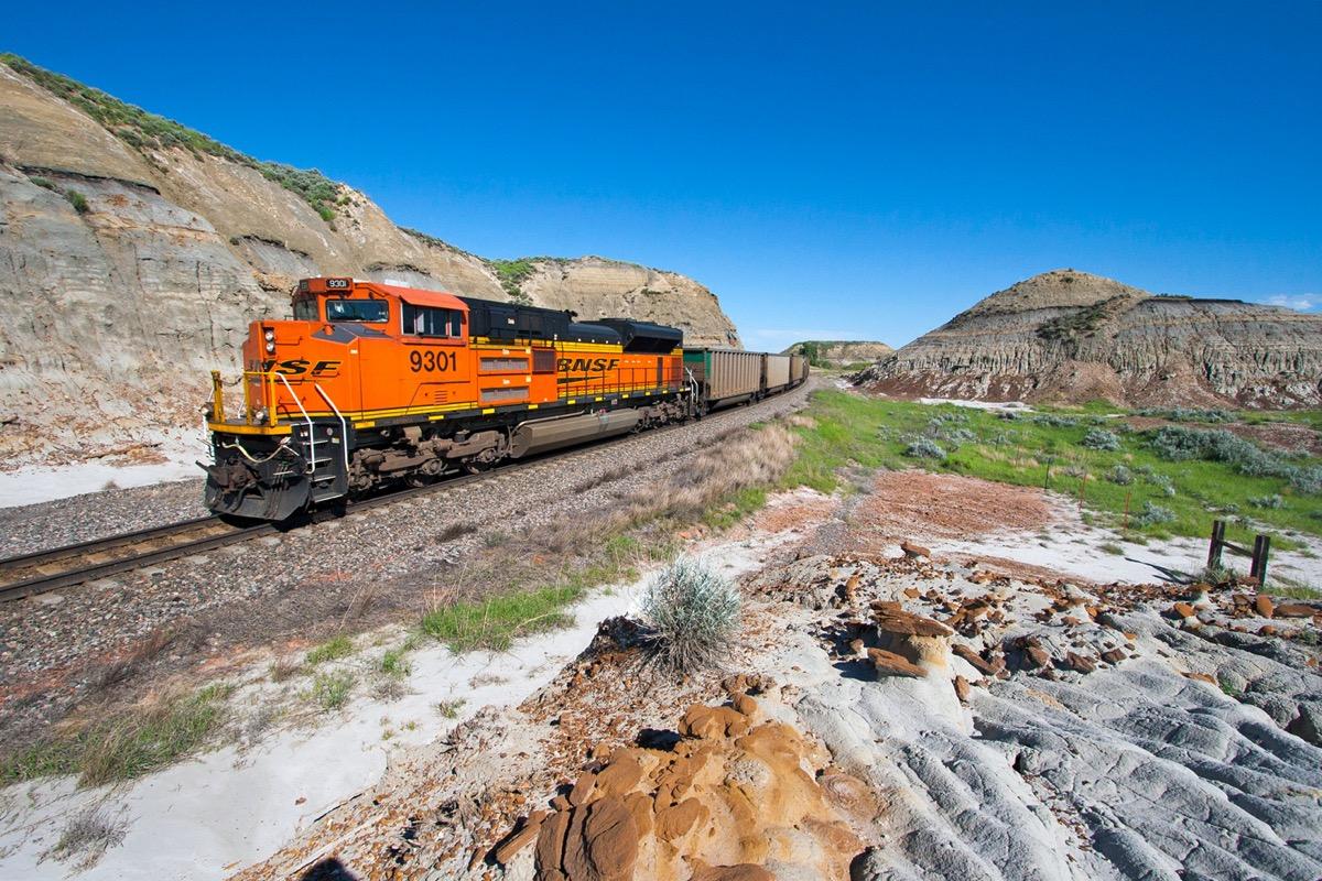 A BNSF Railway locomotive pushes on the rear of an empty coal train in the North Dakota Badlands